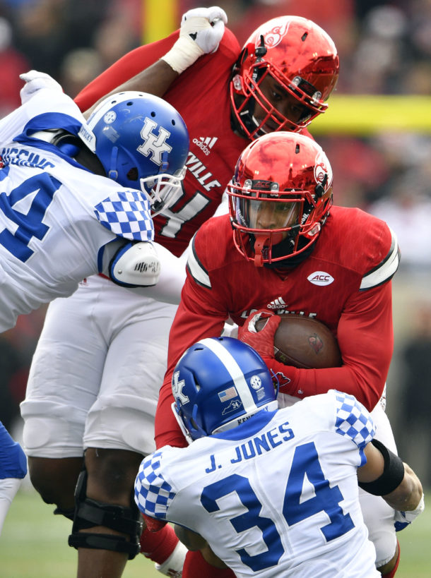 Nov 26, 2016; Louisville, KY, USA; Kentucky Wildcats linebacker Jordan Jones (34) wraps up Louisville Cardinals wide receiver Reggie Bonnafon (7) during the second quarter at Papa John's Cardinal Stadium. Mandatory Credit: Jamie Rhodes-USA TODAY Sports