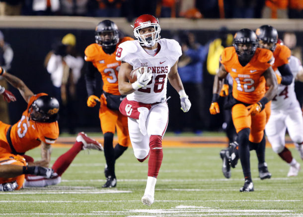 Nov 28, 2015; Stillwater, OK, USA; Oklahoma Sooners running back Alex Ross (28) runs ahead of Oklahoma State Cowboys defense during the first half at Boone Pickens Stadium. Mandatory Credit: Alonzo Adams-USA TODAY Sports