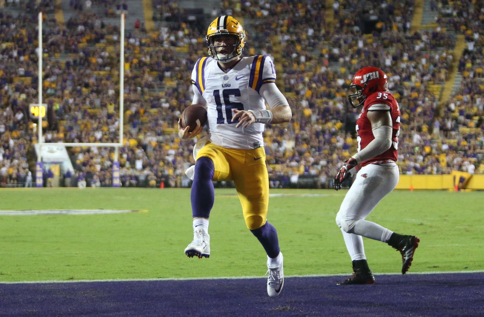 Sep 10, 2016; Baton Rouge, LA, USA; LSU Tigers quarterback Danny Etling (16) runs the ball into the end zone for a touchdown in front of Jacksonville State Gamecocks linebacker Quan Stoudemire (35) during the second half at Tiger Stadium. LSU defeated Jacksonville State 34-13. Mandatory Credit: Crystal LoGiudice-USA TODAY Sports