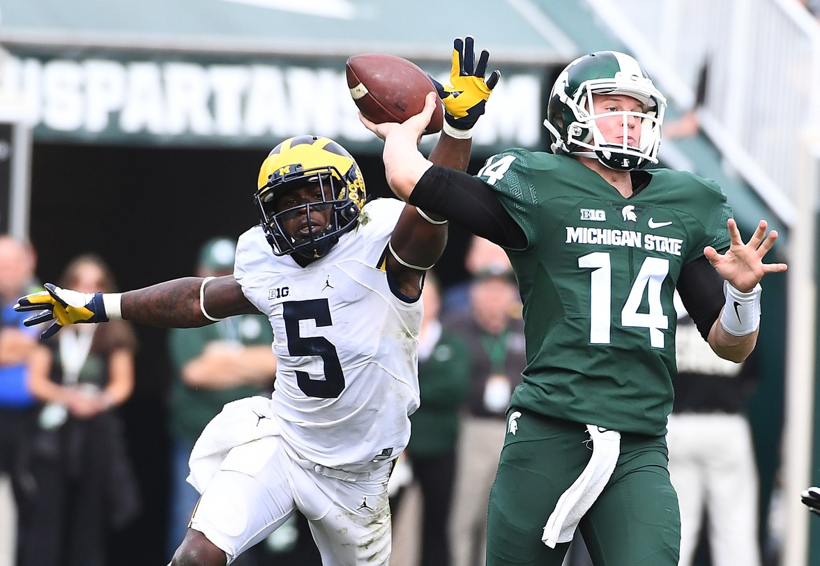 Oct 29, 2016; East Lansing, MI, USA; Michigan State Spartans quarterback Brian Lewerke (14) attempts a pass as Michigan Wolverines linebacker Jabrill Peppers (5) defends during the second half at Spartan Stadium. Mandatory Credit: Brad Mills-USA TODAY Sports