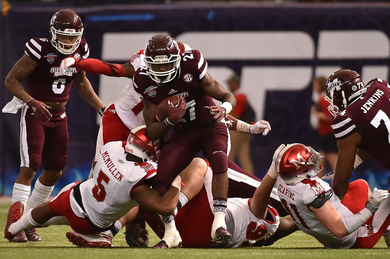 Dec 26, 2016; St. Petersburg, FL, USA; Miami Redhawks defensive back Tony Reid (14) and Miami Redhawks linebacker Junior McMullen (5) bring down Mississippi State Bulldogs running back Aeris Williams (27) during the first half at Tropicana Field. Mandatory Credit: Jasen Vinlove-USA TODAY Sports